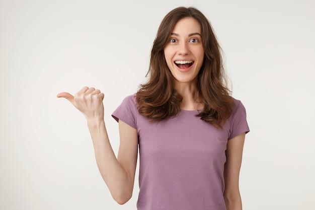 Close-up van verrast verbaasd aantrekkelijke tiener in t-shirt opzij wijzend met neergelaten kaak Gratis Foto