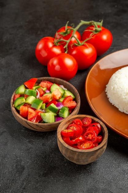 Close-up van verschillende soorten groenten en rijst op een bruine plaat op donker Gratis Foto