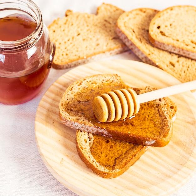 Close-up van verse broodjesplak met honing in houten plaat Gratis Foto