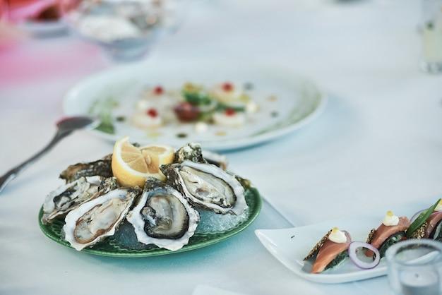 Close-up van verse oesters met citroen op de restaurantlijst. Premium Foto