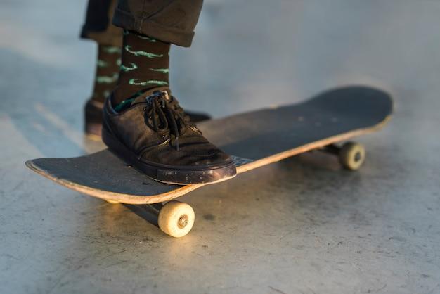Close-up van voeten oefenen met het skateboard Gratis Foto