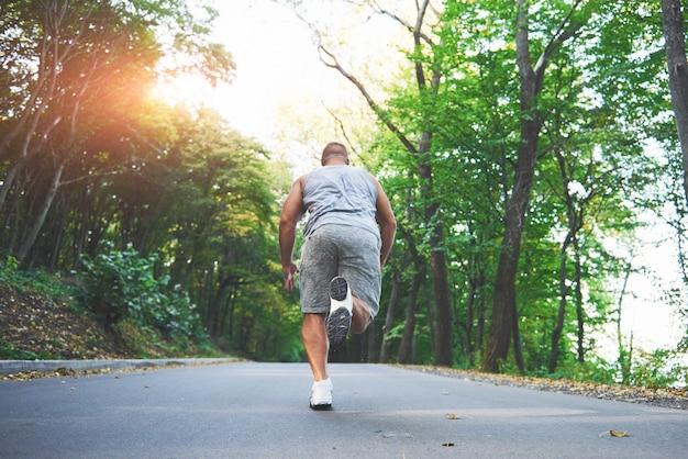 Close up van voeten van jonge atleet man loopt langs de weg in park. Gratis Foto