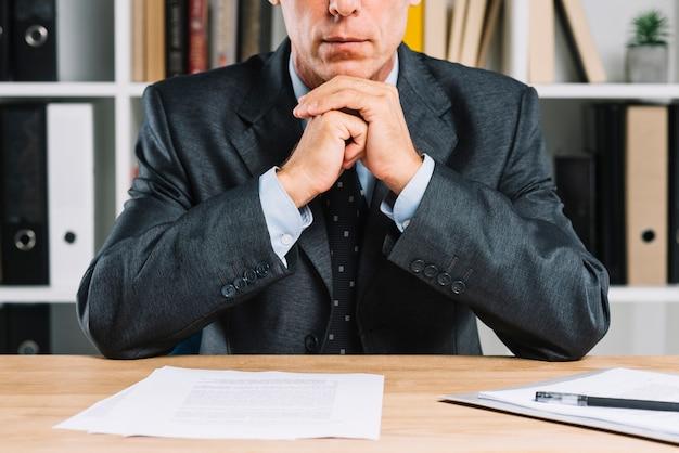 Close-up van volwassen zakenman met document papier op het bureau Premium Foto