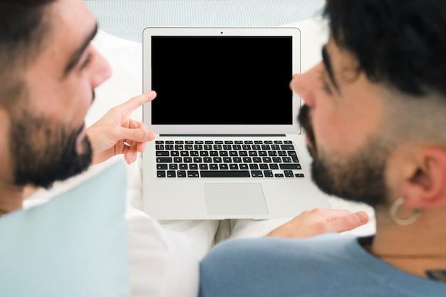 Close-up van vriend die de mens bekijkt die vinger over de laptop monitor richt Gratis Foto
