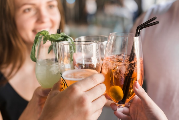 Close-up van vrienden die glazen cocktail roosteren Gratis Foto