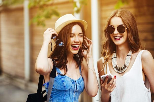 Close-up van vrienden lachen en luisteren naar muziek Gratis Foto