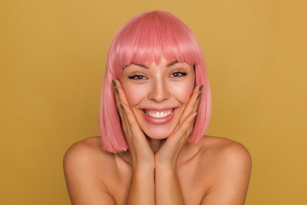 Close-up van vrolijke jonge blauwogige roze harige vrouw met kort trendy kapsel die de handpalmen op haar wangen houdt terwijl ze gelukkig kijkt met een brede glimlach, geïsoleerd over mosterdmuur Gratis Foto