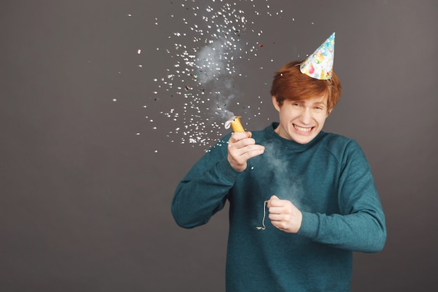 Close up van vrolijke jonge roodharige man met kort kapsel in groene modieuze trui en feestmuts Gratis Foto