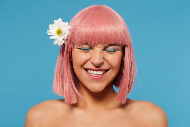 Close-up van vrolijke jonge roze harige mooie vrouw met feestelijke make-up bloem in haar hoofd dragen terwijl poseren op blauwe achtergrond, haar gezicht fronsen terwijl gelukkig lachend Gratis Foto