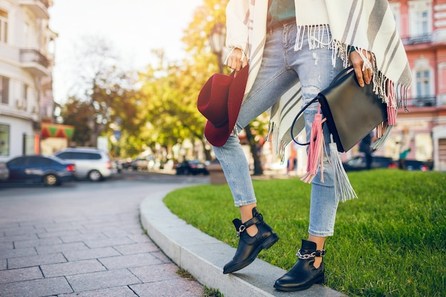 Close up van vrouw benen dragen zwarte lederen laarzen, jeans, schoeisel lente trends, tas te houden Gratis Foto