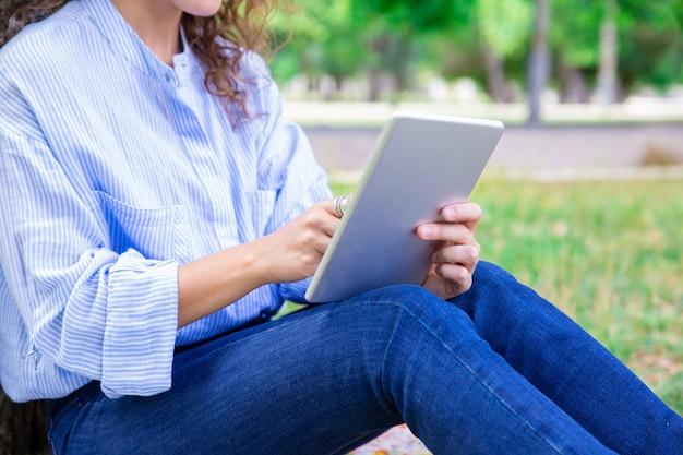 Close-up van vrouw die digitale tablet in de zomerpark gebruiken Gratis Foto