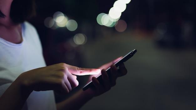 Close-up van vrouw die een smartphone houdt bij nacht op straat. technologie voor communicatieconcept. Premium Foto