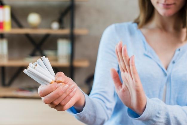 Close-up van vrouw die geen holdingsbos van sigaretten ter beschikking zegt Gratis Foto