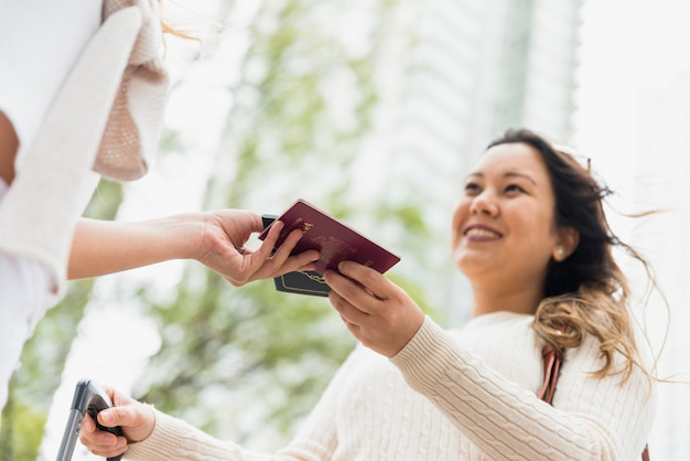 Close-up van vrouw die paspoort geeft aan haar vrouwelijke toeristenvriend in openlucht Gratis Foto