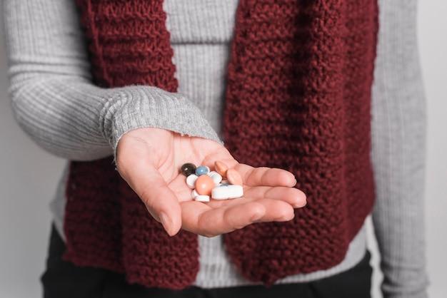 Close-up van vrouw die vele pillen in hand houdt Gratis Foto