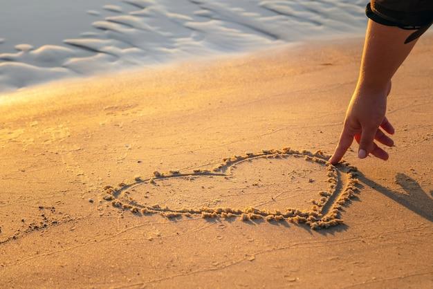 Close-up van vrouw hand hart met vinger tekenen op het zand op het strand. Premium Foto