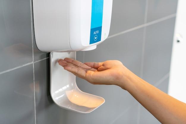 Close up van vrouw hand met behulp van alcohol gel desinfecterende handen. Premium Foto