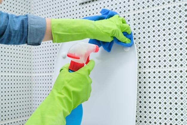 Close up van vrouw in handschoenen met doek en wasmiddel schoonmaken toiletpot, huis schoonmaken in de badkamer Premium Foto