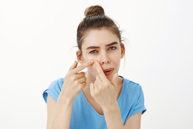 Close-up van vrouw popping puistje, acne verwijderen uit wang Gratis Foto