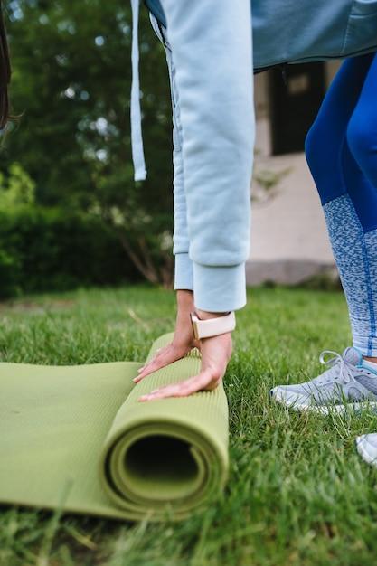 Close-up van vrouw roll fitness of yoga mat vouwen na het trainen in het park Gratis Foto