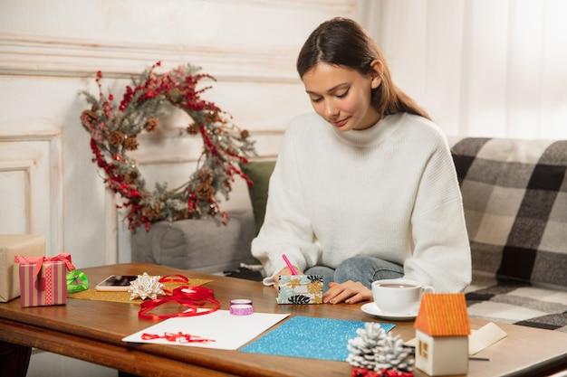 Close-up van vrouw wenskaart maken voor nieuwjaar en kerstmis 2021 voor vrienden of familie, schroot boeken, diy. schrijf een brief met de beste wensen, ontwerp haar zelfgemaakte kaart. vakantie, feest. Gratis Foto