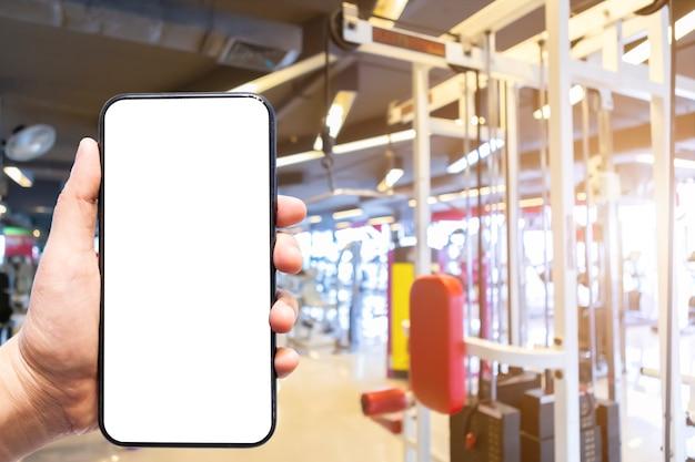 Close-up van vrouwelijk gebruik hand met smartphone wazig beelden aanraking van abstracte vervaging van onscherpe sport sportschool interieur en fitness health club met sport oefeningsapparatuur gym wazige achtergrond. Premium Foto