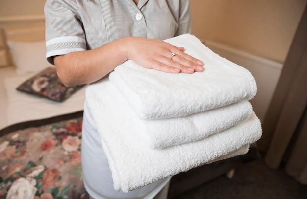 Close-up van vrouwelijk kamermeisje die schone zachte gevouwen handdoek in hand houden Gratis Foto