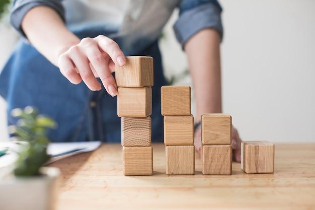 Close-up van vrouwelijke hand die houten blok op bureau op kantoor stapelt Premium Foto