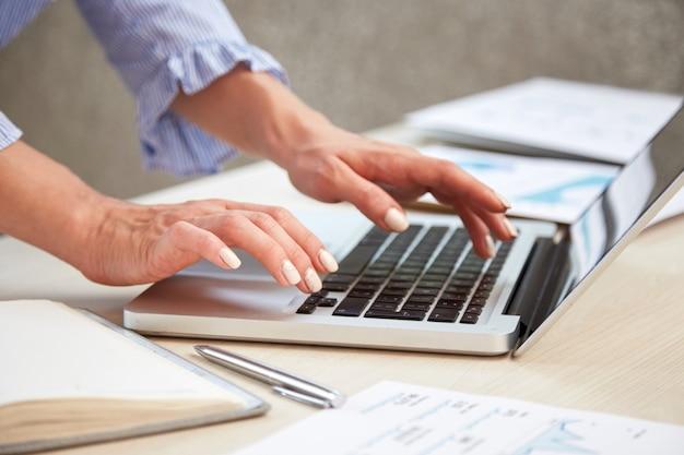 Close-up van vrouwelijke handen die op laptop toetsenbord typen Gratis Foto