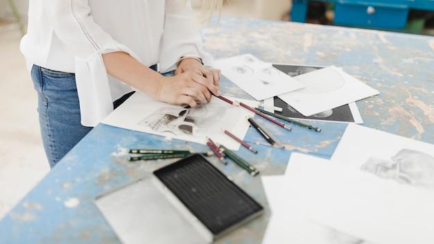 Close-up van vrouwelijke kunstenaarstekening met potlood op werkbank Gratis Foto