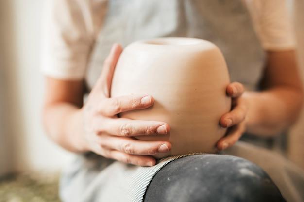 Close-up van vrouwelijke potter die kleipot op haar overlapping houdt Gratis Foto