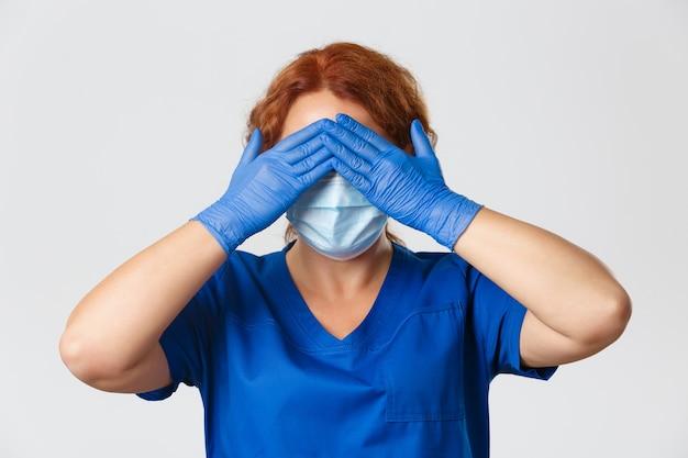 Close-up van vrouwelijke verpleegster of arts in gezichtsmasker, rubberen handschoenen en scrubs sluit ogen met handen, anticiperend, geblinddoekt staan Gratis Foto