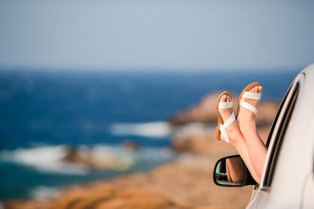 Close-up van vrouwelijke voeten die van autoraam achtergrondoverzees tonen Premium Foto