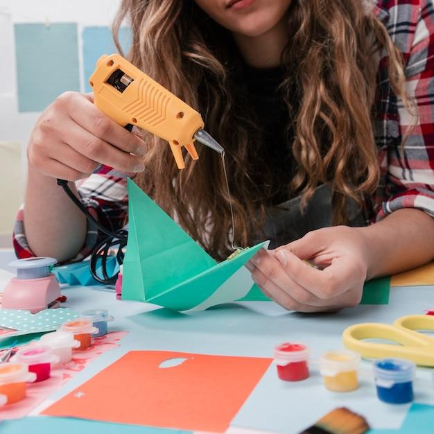 Close-up van vrouwen klevend document met heet lijmpistool Gratis Foto