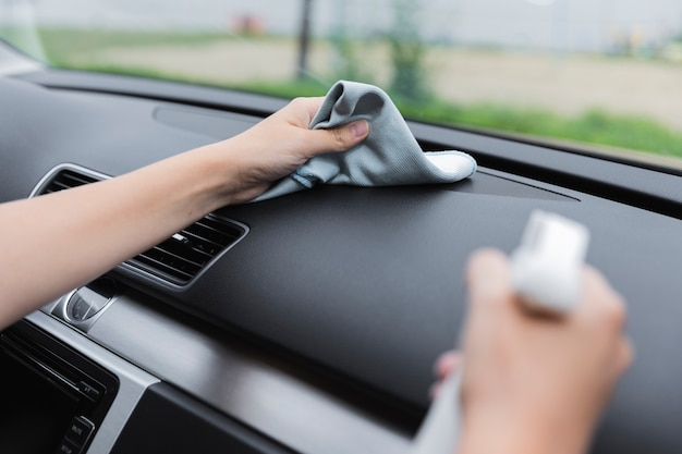 Close-up van vrouwen schoonmakend dashboard Gratis Foto