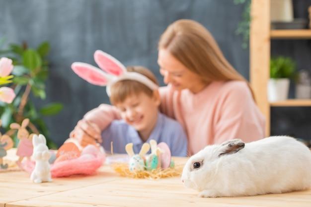 Close-up van wit pluizig konijn dat op houten lijst met paasdecoratie ligt, moeder die zoon koestert Premium Foto