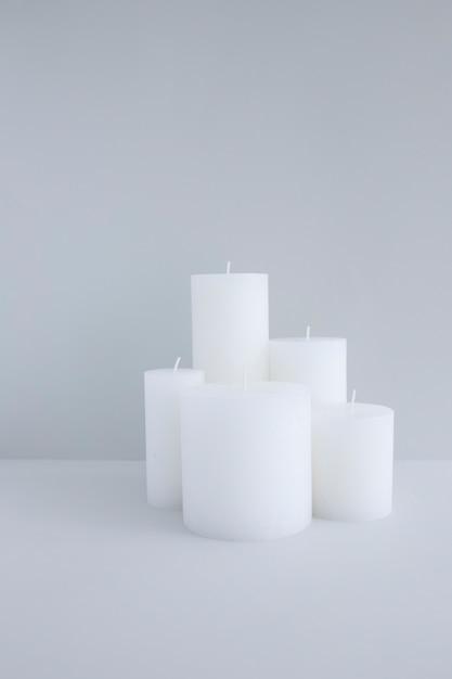 Close-up van witte kaarsen tegen grijze achtergrond Gratis Foto