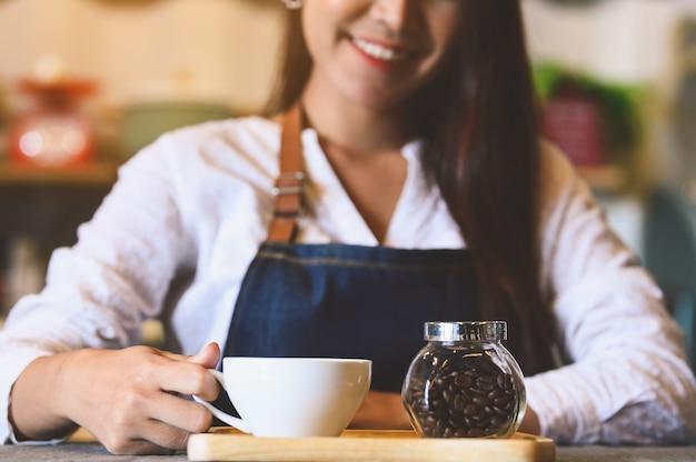 Close-up van witte koffiekop met mooie aziatische vrouwenbarista Premium Foto