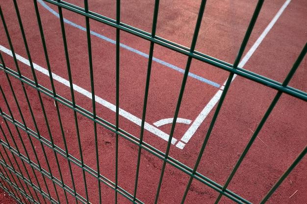 Close-up van witte markering lijnen van buiten basketbalveld omheind met beschermende metalen hek. Premium Foto