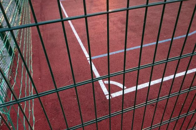 Close-up van witte markering lijnen van outdoor basketbalveld omheind met beschermende metalen hek. Premium Foto