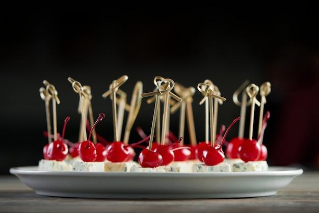 Close-up van witte ronde plaat vol heerlijke hapjes met rode cocktailkersen en schimmelkaasstukken. goede snack voor lichte alcoholische catering of restaurantbuffet. Gratis Foto