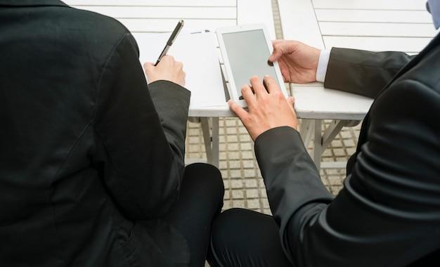 Close-up van zakenman en onderneemster die slimme telefoon houden en op papier bij in openlucht schrijven Gratis Foto