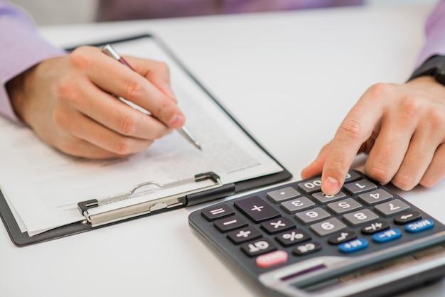 Close-up van zakenman facturen met calculator berekenen Gratis Foto