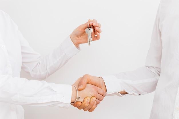 Close-up van zakenman het schudden hand terwijl het geven van sleutels op witte achtergrond Gratis Foto