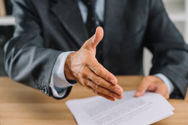 Close-up van zakenman uitgestoken hand voor handdruk Premium Foto