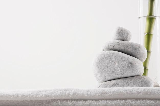 Close-up van zenstenen en bamboeinstallatie in vaas op witte die handdoek op witte achtergrond wordt geïsoleerd Gratis Foto