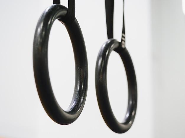 Close-up van zwarte crossfit-ringen op witte muur Premium Foto