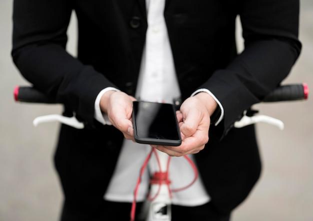 Close-up volwassen mannetje dat mobiele telefoon houdt Gratis Foto