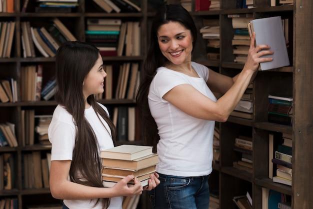 Close-up volwassen vrouw en jong meisje bij de bibliotheek Gratis Foto