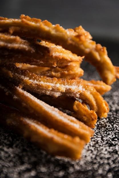 Close-up vooraanzicht gebakken churros en suiker Gratis Foto